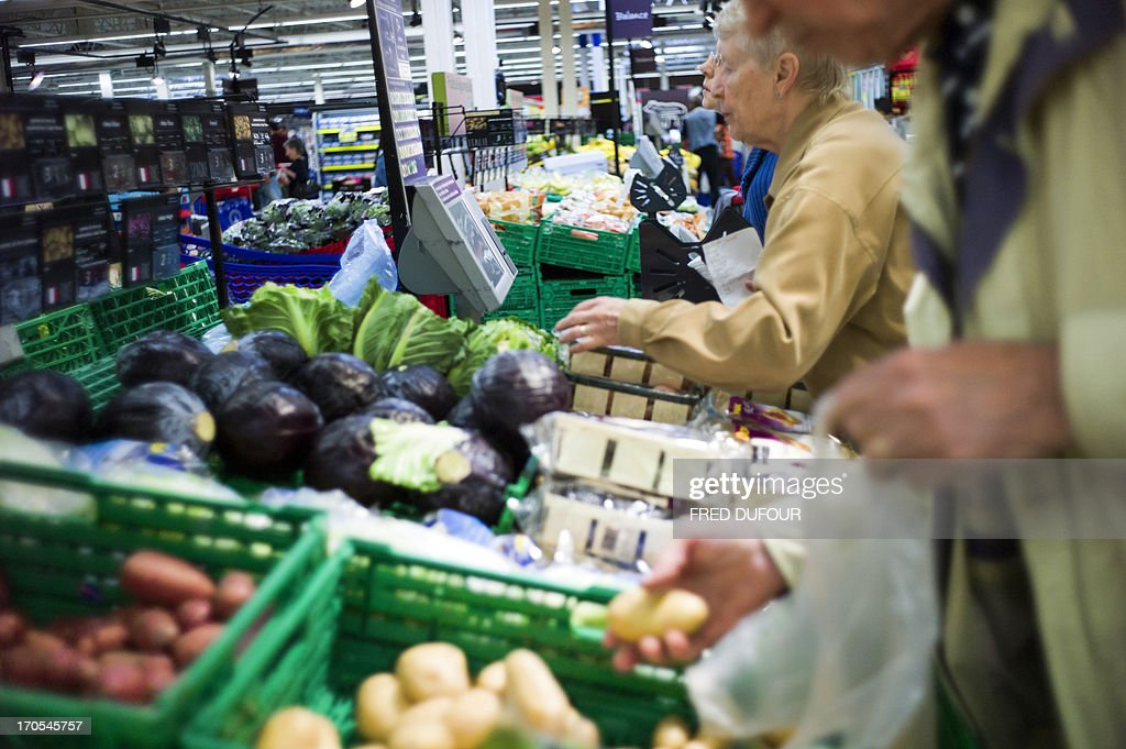 Customers look at vegetables in a Carrefour supermarket, on June 14, 2013 in Sainte-Geneviève-des-Bois, outside Paris. Installed in Sainte-Geneviève-des-Bois since fifty years, on June 15, 1963, this supermarket is the first of French giant retailer Carrefour group, but also the first in France. AFP PHOTO / FRED DUFOUR