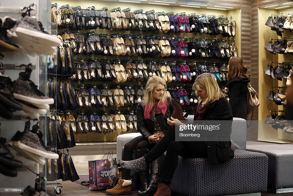 Customers look at women's boots in the shoe department of a Topshop store, owned by Arcadia Group Ltd., on Oxford Street in London, U.K., on Thursday, Dec. 6, 2012. Philip Green, the billionaire owner of the Arcadia fashion business, sold a 25 percent stake in the Topshop and Topman retail chains to Leonard Green & Partners LP, the co-owner of the J Crew fashion brand, in a deal valuing the businesses at 2 billion pounds ($3.2 billion). Photographer: Simon Dawson/Bloomberg via Getty Images