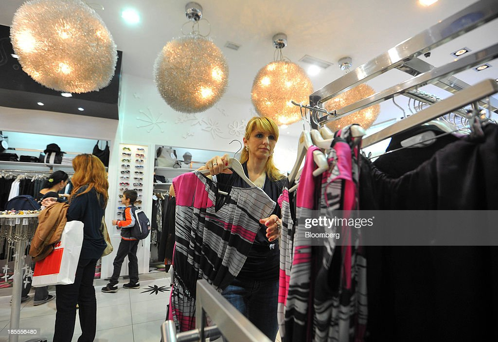 Customers look at women's fashion clothing on display in a retail store in Belgrade, Serbia, on Monday, Oct. 21, 2013. Serbia's government revealed a salvo of measures to bring the public finance deficit and debt back under control by 2017 after the head of the largest coalition party warned the country was on the brink of insolvency. Photographer: Oliver Bunic/Bloomberg via Getty Images