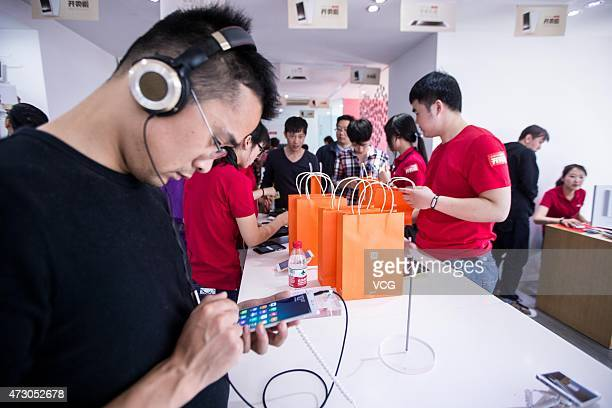 Customers look at Xiaomi phones during the first day of the high configuration Xiaomi Note to be on sale at a Xiaomi experience store on May 12 2105...