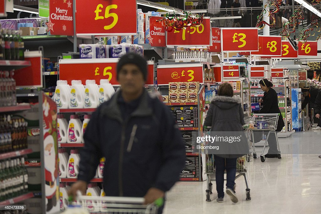 Customers look for groceries as they push shopping carts along the shopping aisles inside an Asda supermarket in Wembley, London, U.K., on Friday, Nov. 29, 2013. Britons queued outside Asda supermarkets this morning and charged into stores when doors opened at 8 a.m. as the U.K. grocery chain took on the Black Friday mantle from U.S. owner Wal-Mart Stores Inc. Photographer: Simon Dawson/Bloomberg via Getty Images