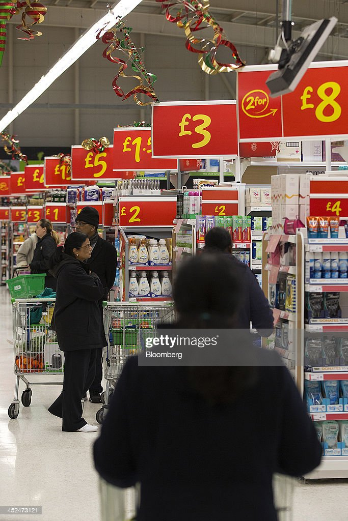 Customers look for groceries as they walk along the shopping aisles inside an Asda supermarket in Wembley, London, U.K., on Friday, Nov. 29, 2013. Britons queued outside Asda supermarkets this morning and charged into stores when doors opened at 8 a.m. as the U.K. grocery chain took on the Black Friday mantle from U.S. owner Wal-Mart Stores Inc. Photographer: Simon Dawson/Bloomberg via Getty Images