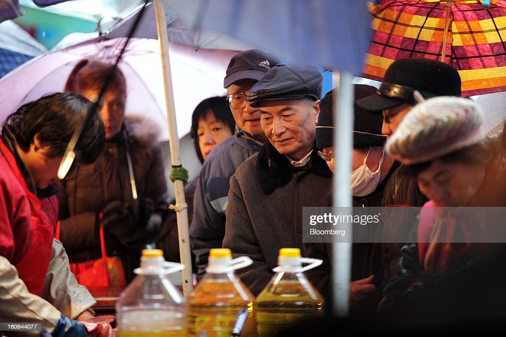 Customers look on as a vendor cooks food at a market stall in Shanghai, China, on Thursday, Feb. 7, 2013. China's consumer prices rose 2 percent in January from a year earlier while the producer-price index dropped 1.6 percent, the National Bureau of Statistics said today in Beijing. Photographer: Tomohiro Ohsumi/Bloomberg via Getty Images