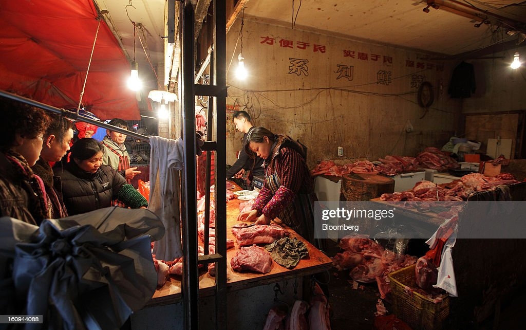 Customers look on as butchers prepare cuts of meat at a market in Shanghai, China, on Thursday, Feb. 7, 2013. China's consumer prices rose 2 percent in January from a year earlier while the producer-price index dropped 1.6 percent, the National Bureau of Statistics said today in Beijing. Photographer: Tomohiro Ohsumi/Bloomberg via Getty Images
