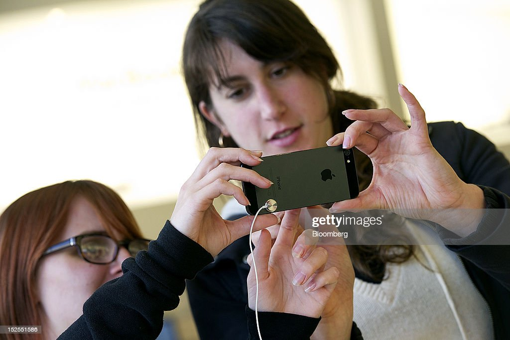 Customers look over an Apple Inc. iPhone 5 at a store in San Francisco, California, U.S., on Friday, Sept. 21, 2012. Apple Inc. is poised for a record iPhone 5 debut and may not be able to keep up with demand as customers lined up in Sydney, Tokyo, Paris and New York to pick up the latest model of its top-selling product. Photographer: David Paul Morris/Bloomberg via Getty Images