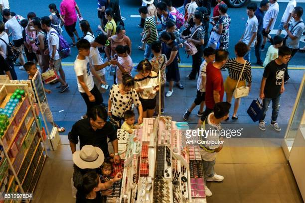 Customers look through the products inside a store in Shanghai on August 14 2017 China's industrial output a key engine of growth slowed sharply in...