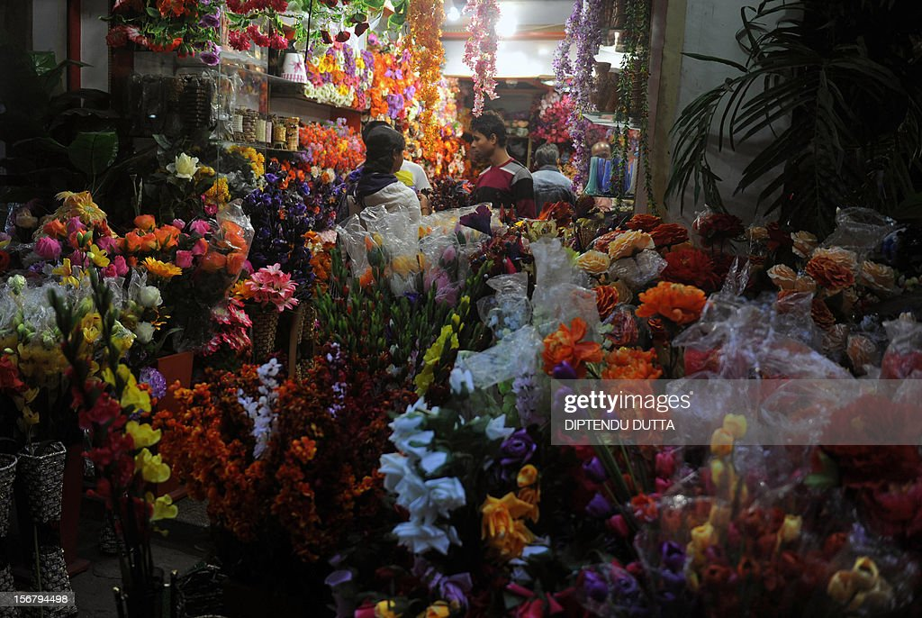 Customers looks at artificial flowers at a market in Siliguri on November 21, 2012. Widening income gaps and rising numbers of unskilled young people could derail India's economic growth, speakers at a high-profile economic conference warned on November 8. AFP PHOTO/Diptendu DUTTA