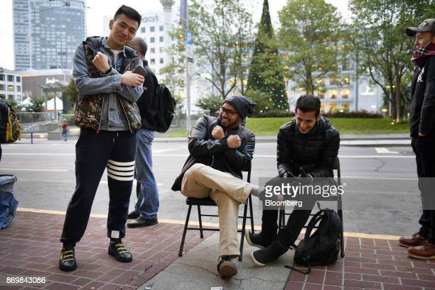 Customers make an 'X' gesture while waiting in line outside a store ahead of the sales launch for the Apple Inc iPhone X smartphone in San Francisco...