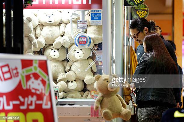Customers operate a claw crane machines with stuffed animal toys at a Taito Corp game arcade in Tokyo Japan on Thursday Dec 11 2014 Japanese stocks...