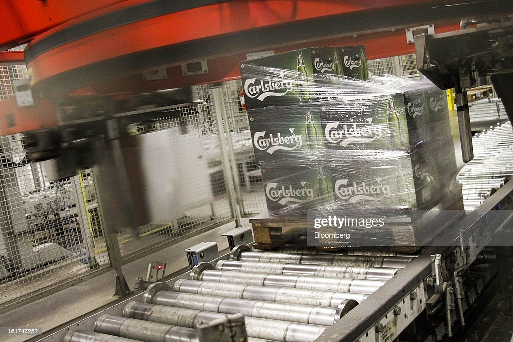 A customer's order of Carlsberg bottled beer moves along a conveyor belt after being wrapping in plastic at the Carlsberg A/S East Terminal distribution depot in Tastrup, Denmark, on Thursday, Feb. 14, 2013. Danish brewer Carlsberg A/S owns France's biggest beer brand Kronenbourg. Photographer: Freya Ingrid Morales/Bloomberg via Getty Images