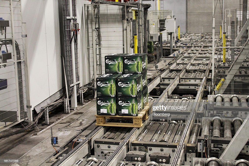 A customer's order of Carlsberg bottled beer moves along a conveyor belt before wrapping in plastic at the Carlsberg A/S East Terminal distribution depot in Tastrup, Denmark, on Thursday, Feb. 14, 2013. Danish brewer Carlsberg A/S owns France's biggest beer brand Kronenbourg. Photographer: Freya Ingrid Morales/Bloomberg via Getty Images