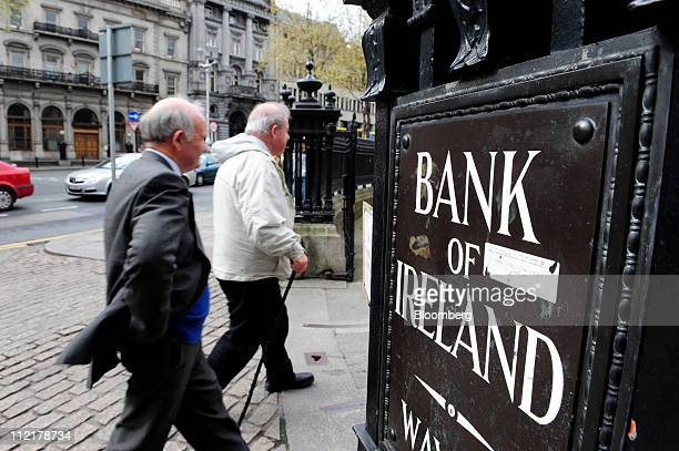 Customers pass a Bank of Ireland automated sign outside a branch in Dublin Ireland on Thursday April 14 2011 Bank of Ireland Plc said it will outline...