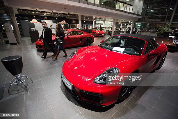 Customers pass a Porsche Boxter sportscar right for sale inside a Porsche AG luxury automobile dealership in Moscow Russia on Monday Dec 15 2014...