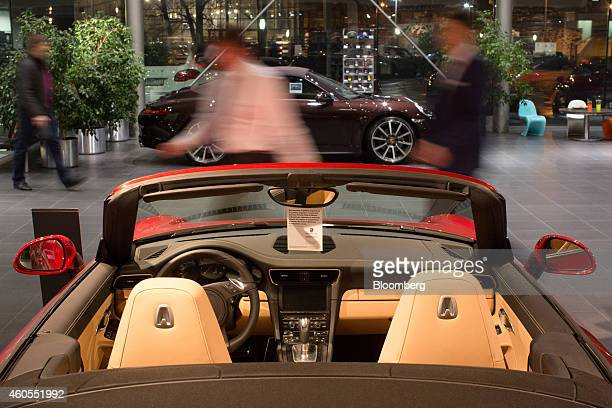 Customers pass luxury sportscars for sale inside a Porsche AG luxury automobile dealership in Moscow Russia on Monday Dec 15 2014 Russia's biggest...