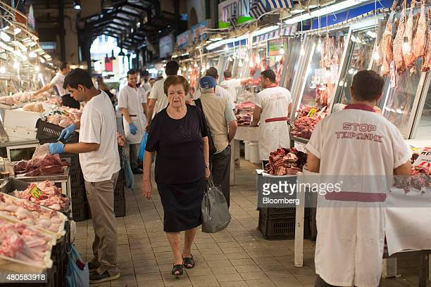 Customers pass meat vendors inside Varvakeios fish and meat market in Athens Greece on Monday July 13 2015 Greece has been in financial limbo since...