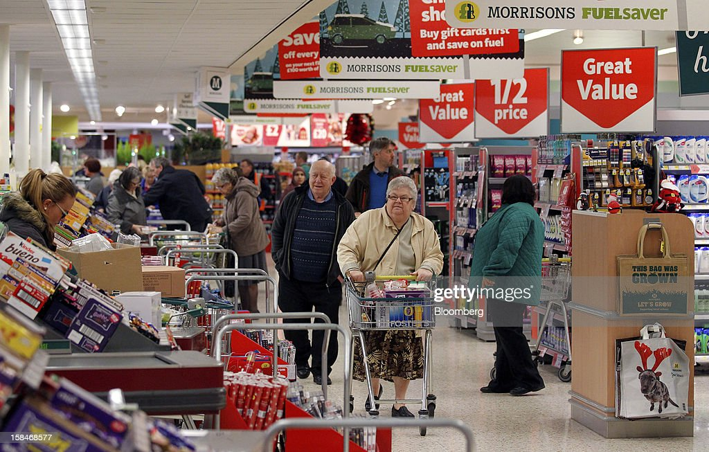 Customers pass shopping aisles inside a Morrisons supermarket, operated by William Morrisons Supermarkets Plc, in Chadderton, U.K., on Monday, Dec. 17, 2012. The British Christmas is the biggest epicurean occasion of the year, with households spending a total of 4 billion pounds on food in the final week before Dec. 25. Photographer: Paul Thomas/Bloomberg via Getty Images