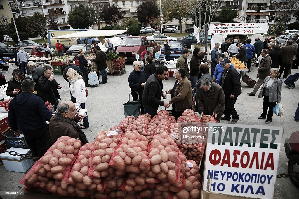 Customers pass stalls selling fresh produce at a farmers' market in Thessaloniki, Greece, on Saturday, Nov. 16, 2013. Greek Prime Minister Antonis Samaras, who survived a no-confidence vote on Nov. 11 with his parliamentary majority reduced to four, is trumpeting the first economic growth in seven years for 2014. Photographer: Konstantinos Tsakalidis/Bloomberg via Getty Images