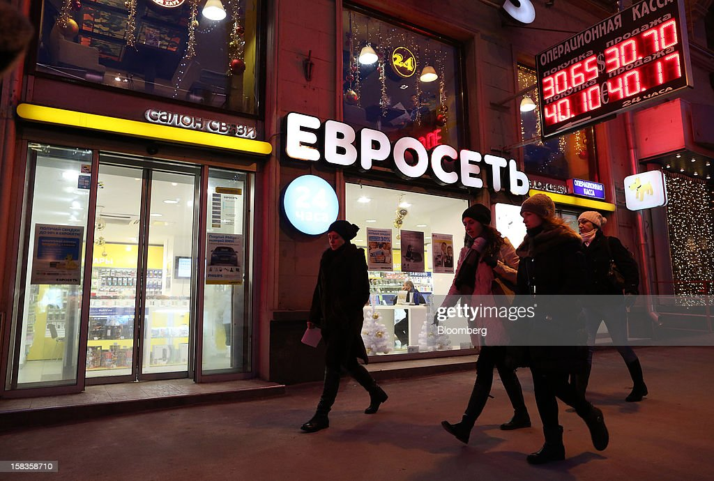Customers pass the illuminated window of a Euroset Holding NV mobile phone store beneath a digital currency exchange board in Moscow, Russia, on Thursday, Dec. 13, 2012. OAO MegaFon and its main shareholder billionaire Alisher Usmanov bought 50 percent of Euroset Holding NV in a deal that gives Russia's biggest handset retailer an enterprise value of $2.3 billion. Photographer: Andrey Rudakov/Bloomberg via Getty Images