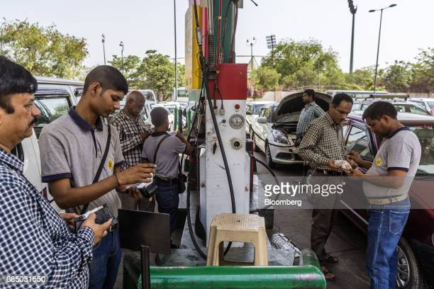 Customers pay after filling their vehicles with compressed natural gas at an Indraprastha Gas Ltd gas station in New Delhi India on Wednesday May 17...