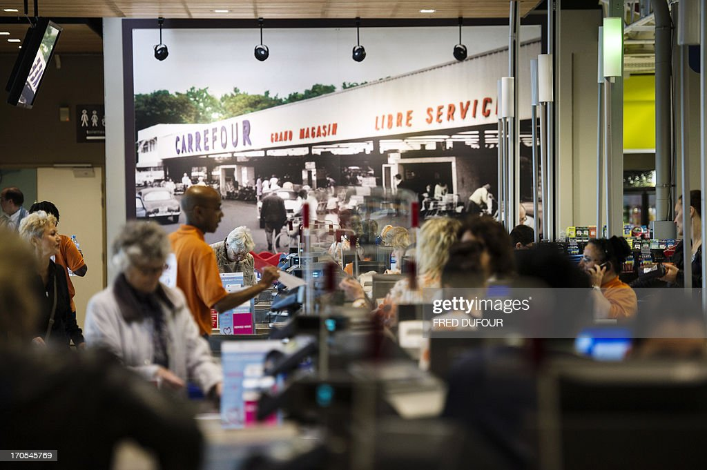 Customers pay at the cashier in a Carrefour supermarket, on June 14, 2013 in Sainte-Geneviève-des-Bois, outside Paris. Installed in Sainte-Geneviève-des-Bois since fifty years, on June 15, 1963, this supermarket is the first of French giant retailer Carrefour group, but also the first in France. In the background, a file picture showing the supermarket in 1963 is seen. AFP PHOTO / FRED DUFOUR