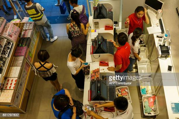 Customers pay bills inside a store in Shanghai on August 14 2017 China's industrial output a key engine of growth slowed sharply in July as...