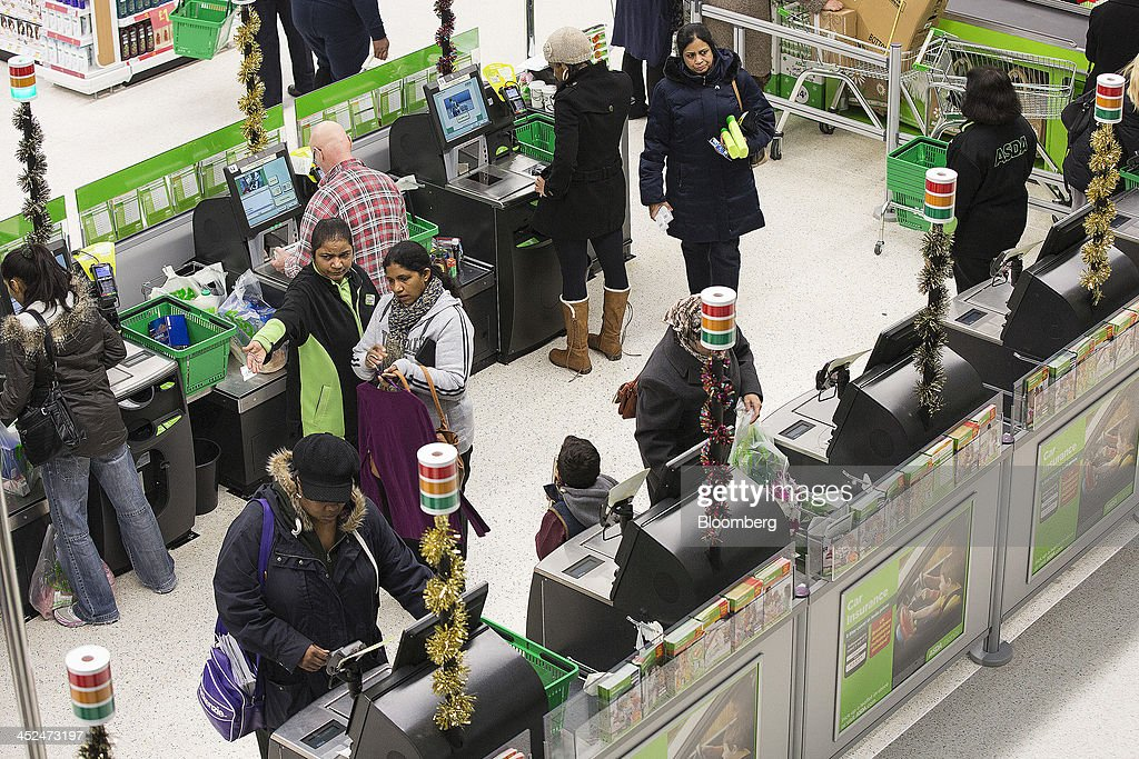 Customers pay for their goods at self-serve check-out desks inside an Asda supermarket in Wembley, London, U.K., on Friday, Nov. 29, 2013. Britons queued outside Asda supermarkets this morning and charged into stores when doors opened at 8 a.m. as the U.K. grocery chain took on the Black Friday mantle from U.S. owner Wal-Mart Stores Inc. Photographer: Simon Dawson/Bloomberg via Getty Images