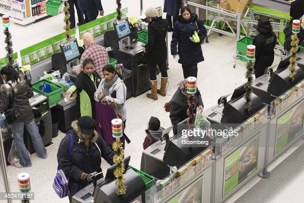 Customers pay for their goods at selfserve checkout desks inside an Asda supermarket in Wembley London UK on Friday Nov 29 2013 Britons queued...