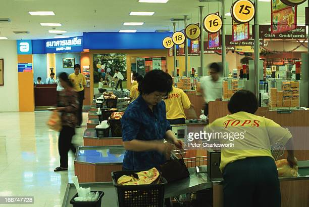 Customers pay for their groceries at the checkout tills of the Tops supermarket inside a large Central department store in downtown Bangkok In the...