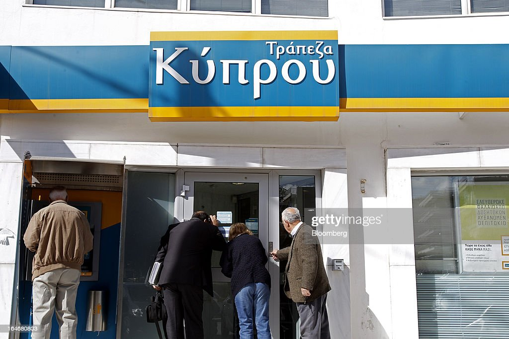 Customers peer through the doors of a closed branch of the Bank of Cyprus Plc in Athens, Greece, on Tuesday, March 26, 2013. Piraeus Bank SA acquires Greek units of Cypriot lenders for total cash consideration of EU524m, according to e-mailed statement from the Athens-based lender today. Photographer: Kostas Tsironis/Bloomberg via Getty Images