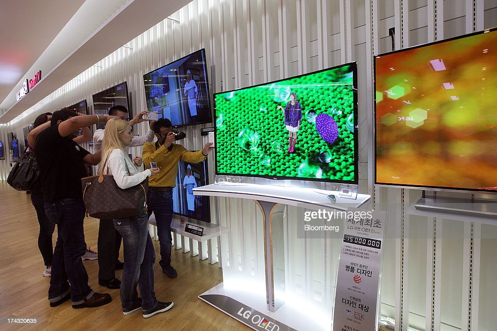 Customers photograph an LG Electronics Inc. curved OLED television at one of the company's bestshop stores in the Gangnam area of Seoul, South Korea, on Wednesday, July 24, 2013. LG Electronics, the worlds second-largest television maker, posted second-quarter profit that missed analyst estimates on slowing demand for sets and increased spending on marketing for smartphones. Photographer: Woohae Cho/Bloomberg via Getty Images