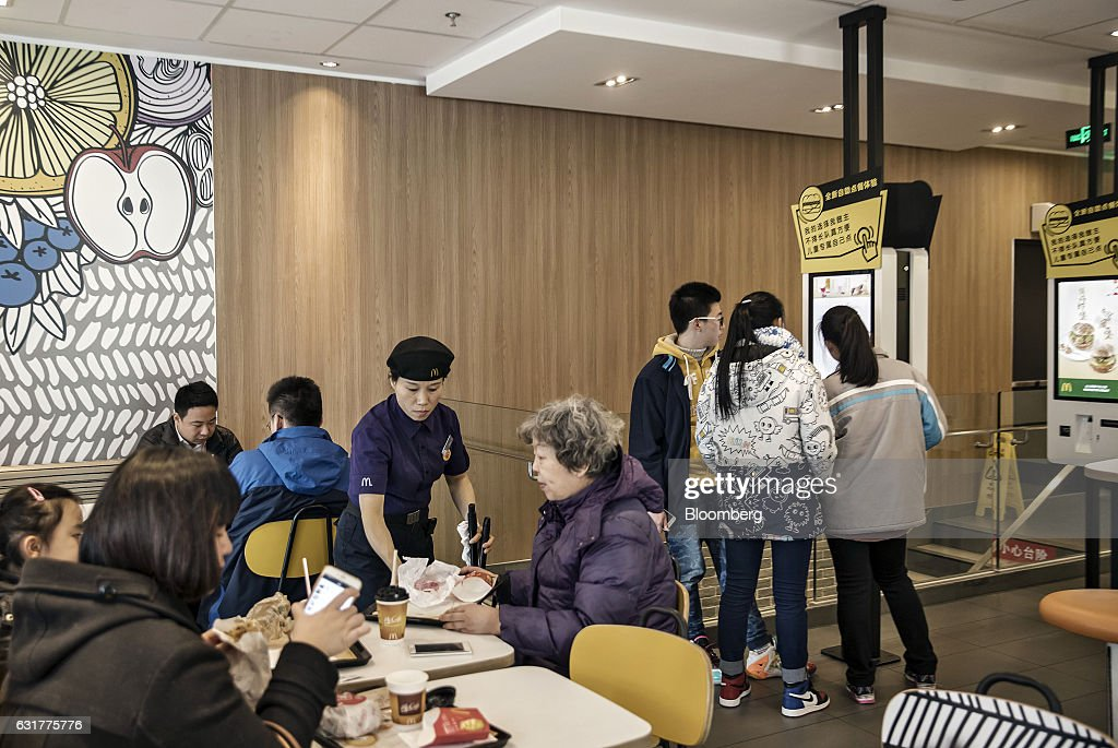 Customers place orders at a touch-screen kiosk as other customers dine inside a McDonald's Corp. restaurant in Shanghai, China, on Friday, Jan. 13, 2017. McDonald's agreed to sell a controlling stake in its China and Hong Kong operations to a group of investors for about $1.7 billion, a key component of the fast-food giants reorganization in a market where its striving to catch up with more nimble rivals. Photographer: Qilai Shen/Bloomberg via Getty Images