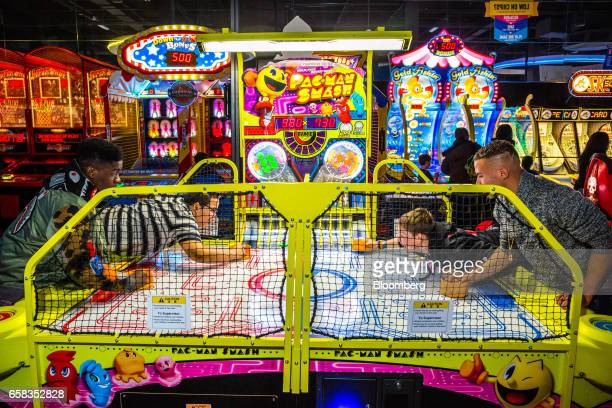 Customers play PacMan Smash air hockey at a Dave Buster's Entertainment Inc location in Pelham New York US on Friday March 24 2017 Dave Buster's...