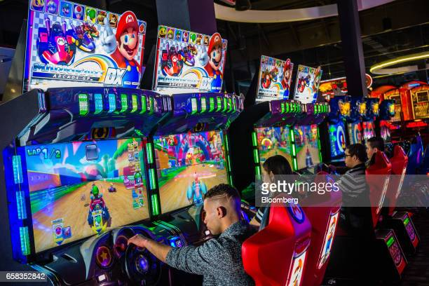 Customers play the Nintendo Co Mario Kart arcade game at a Dave Buster's Entertainment Inc location in Pelham New York US on Friday March 24 2017...