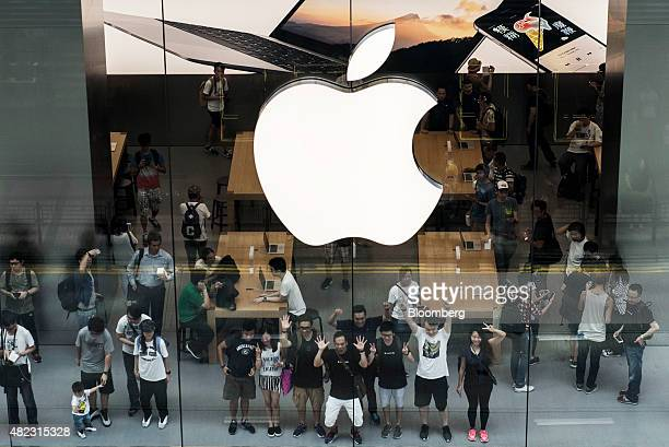 Customers pose for a photograph inside Apple Inc's new Canton Road store in the Tsim Sha Tsui district of Hong Kong China on Thursday July 30 2015...
