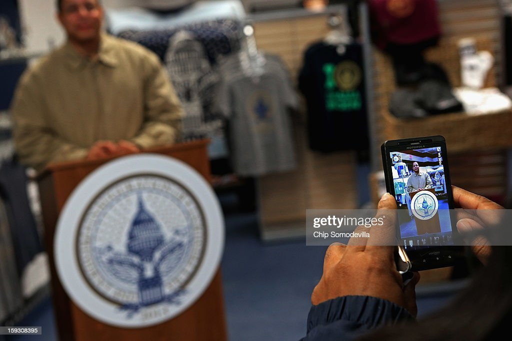 Customers pose for photographs behind a podium with the official inaugural seal at the Presidential Inaugural Committee's store near the intersection of 11th and F Streets NW January 11, 2013 in Washington, DC. A variety of merchandise, from handbags and pencils to throw rugs and limited edition coin sets, will be for sale until the January 21 inauguration of President Barack Obama.