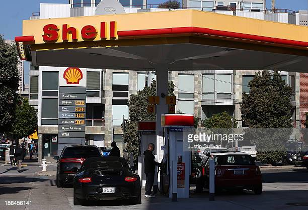 Customers pump gasoline into their cars at a Shell gas station on October 31 2013 in San Francisco California Royal Dutch Shell reported a 32%...