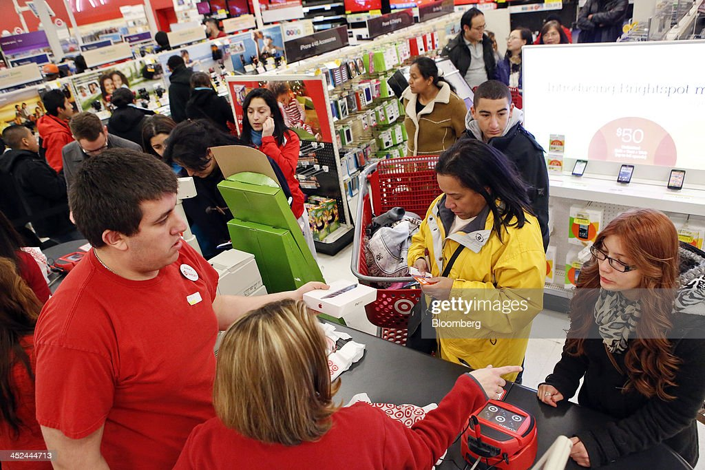 Customers purchase merchandise at a Target Corp. store opening ahead of Black Friday in Chicago, Illinois, U.S., on Thursday, Nov. 28, 2013. U.S. retailers will kick off holiday shopping earlier than ever this year as stores prepare to sell some discounted items at a loss in a battle for consumers. Photographer: Patrick T. Fallon/Bloomberg via Getty Images