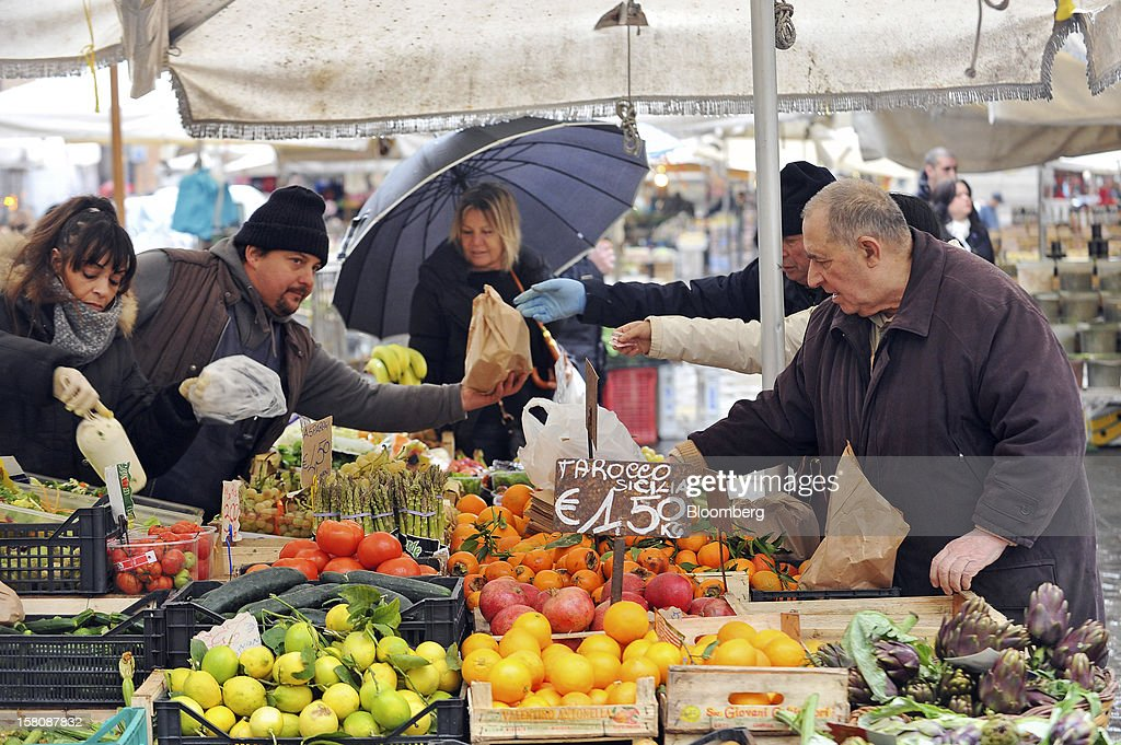 Customers purchase produce from a fruit and vegetable market stall at the Campo dei Fiori market in Rome, Italy, on Monday, Dec. 10, 2012. The imminent end of Prime Minister Mario Monti's government fueled the largest increase in Italian borrowing costs in four months and threatened to open a new front in Europe's crisis fight before a year-end summit. Photographer: Victor Sokolowicz/Bloomberg via Getty Images