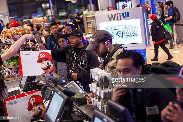 Customers purchase the Mario Kart 8 video game during the release at Nintendo World in New York US on Thursday May 29 2014 Nintendo Co's Mario Kart 8...