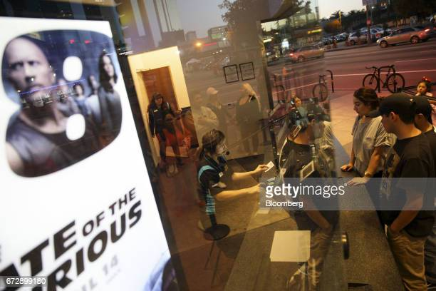 Customers purchase tickets from the box office next to 'The Fate of the Furious' film signage at the Regal Cinemas LA LIVE Stadium 14 movie theater...