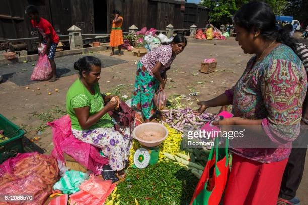Customers purchase vegetables from a street vendor in the Pettah neighborhood of Colombo Sri Lanka on Thursday April 20 2017 The Central Bank of Sri...