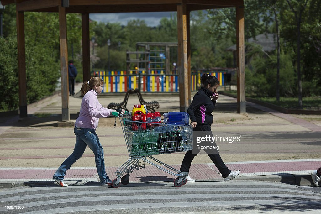 Customers push a cart full of drinks bottles after shopping at a Mercadona supermarket in Madrid, Spain, on Thursday, May 16, 2014. Billionaires Juan Roig and Hortensia Herrero, the husband-and-wife team that controls Mercadona SA, Spain's largest supermarket chain, created thousands of jobs last year as their country's economy crumbled. Photographer: Angel Navarrete/Bloomberg via Getty Images