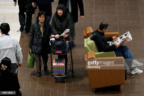 Customers push a shopping cart bearing the Aeon Co logo at the Aeon Mall Makuhari Shintoshin shopping mall operated by Aeon Mall Co in Chiba Japan on...