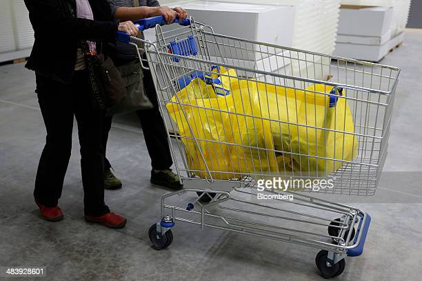 Customers push a shopping trolley with Ikea shopping bags as they shop at an Ikea store in Tokyo Japan on Thursday April 10 2014 Ikea the world's...
