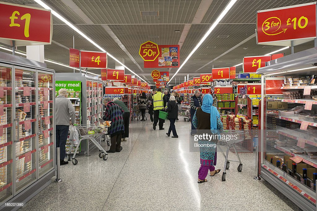 Customers push shopping carts as they browse goods along an aisle inside an Asda supermarket, the U.K. retail arm of Wal-Mart Stores Inc., in Watford, U.K., on Thursday, Oct. 17, 2013. U.K. retail sales rose more than economists forecast in September as an increase in furniture demand led a rebound from a slump the previous month. Photographer: Simon Dawson/Bloomberg via Getty Images