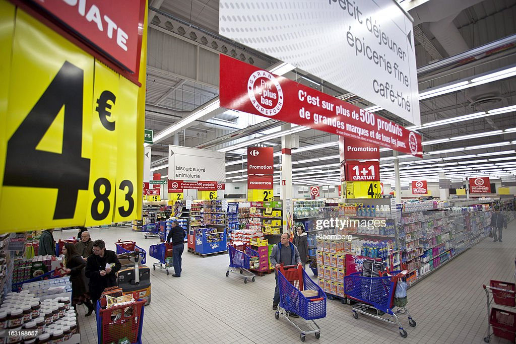 Customers push shopping carts as they browse products on offer inside a Carrefour SA supermarket in Portet sur Garonne, near Toulouse, France, on Tuesday, March 5, 2013. Carrefour's stock has risen 47 percent since Georges Plassat's arrival as chief executive officer, partially offsetting a 71 percent decline in the preceding five years. Photographer: Balint Porneczi/Bloomberg via Getty Images
