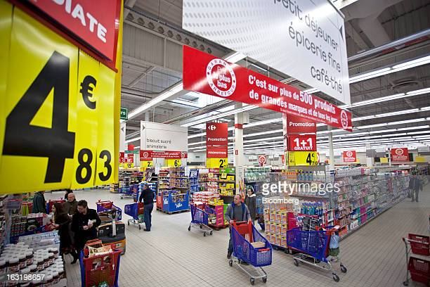 Customers push shopping carts as they browse products on offer inside a Carrefour SA supermarket in Portet sur Garonne near Toulouse France on...