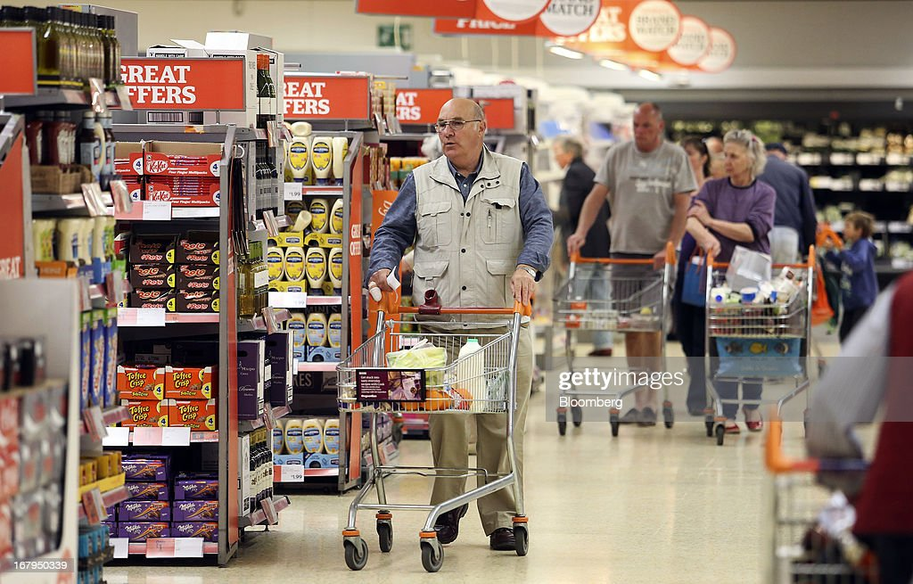 Customers push shopping carts as they look for goods inside a Sainsbury's supermarket store, operated by J Sainsbury Plc, in Godalming, U.K., on Thursday, May 2, 2013. J Sainsbury Plc, the U.K.'s third-largest supermarket chain, will report full year results on May 8. Photographer: Chris Ratcliffe/Bloomberg via Getty Images