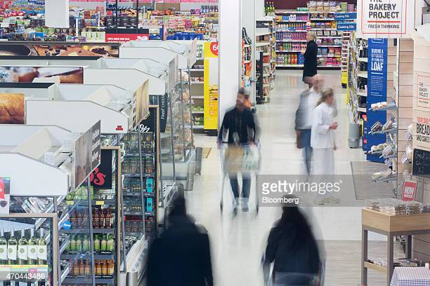 Customers push shopping carts as they shop for goods inside a Tesco supermarket operated by Tesco Plc in London UK on Monday April 20 2015 Tesco's...