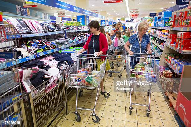Customers push shopping carts as they walk through the shopping aisles inside an Aldi supermarket store in London UK on Monday June 29 2015 The...